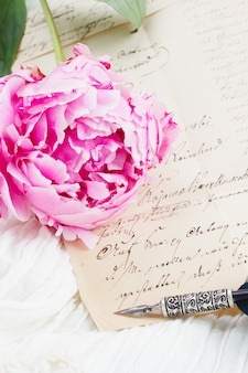 Pink peony with antique letter and feather pen on white lace