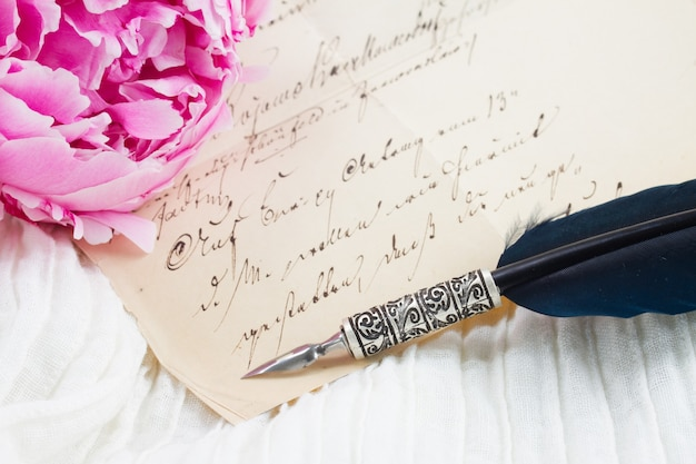 Pink peony with antique letter and feather pen