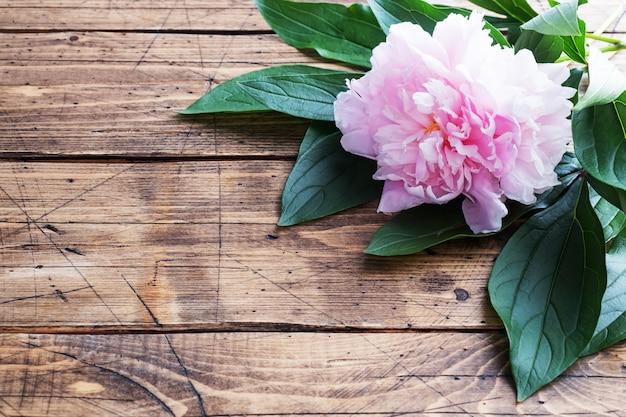 木製の背景の葉とピンクの牡丹