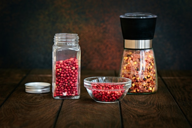 Pink pepper and a mixture of spices in glass jars on a dark background, shallow depth of field