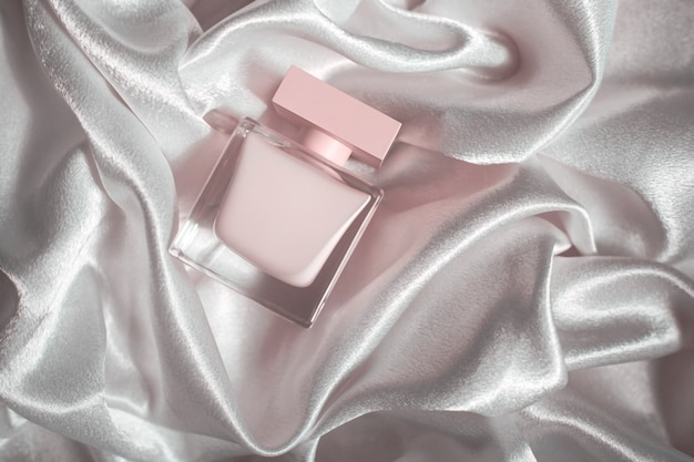 Pink perfume on a background of silk fabric
