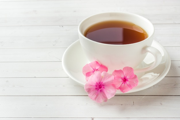 Pink phlox flowers and a cup of coffee on a white table.