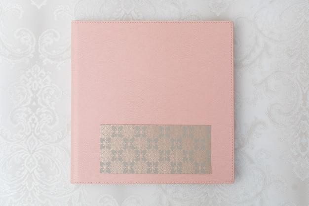 革カバー付きのピンクの写真集。テキスト用のコピースペースが付いたハードカバー付きのフォトアルバム。写真の公開用。サンプル写真集。シールド付き写真集をクローズアップ。