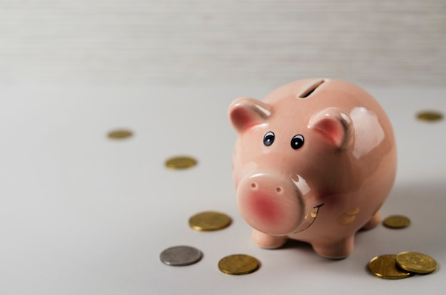 Pink pig money box with coins on wooden background