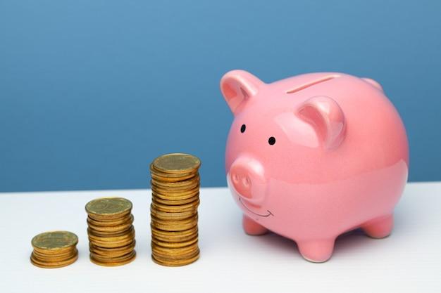 ピンクの貯金箱とテーブルの階段の上のコインのスタック