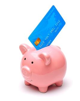 ピンクの貯金箱と白い背景で隔離のスタックのクレジットカードお金を節約する方法