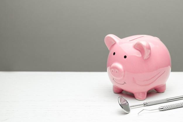 ピンクの貯金箱と灰色の歯科用ツール。歯科治療を節約する方法の概念。テキストのスペースをコピーします。