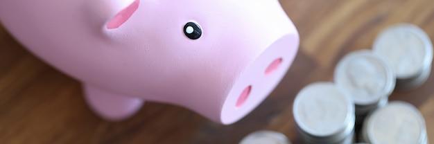 나무 테이블에 서 있는 분홍색 돼지 저금통과 은화
