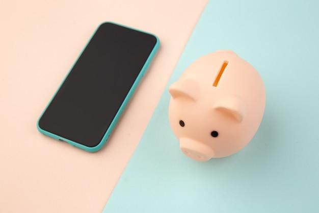 ピンクの貯金箱と株式市場のスマートフォン。コンセプトを保存します。