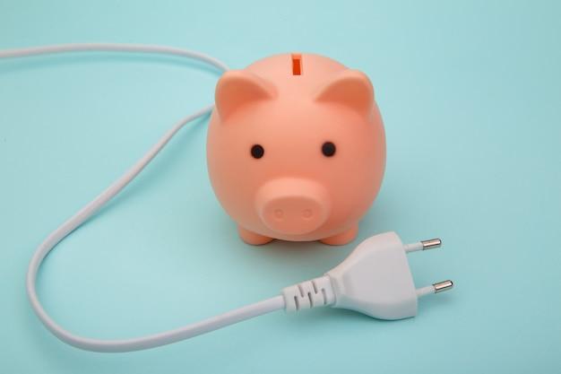 ピンクの貯金箱と白いコード、省電力コンセプト