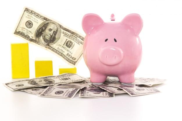 Pink piggy bank beside graph on dollars