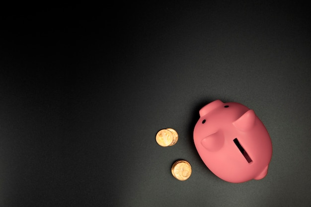 Pink piggy bank on a black background top view with copy spacesavingsfinancial and business concept
