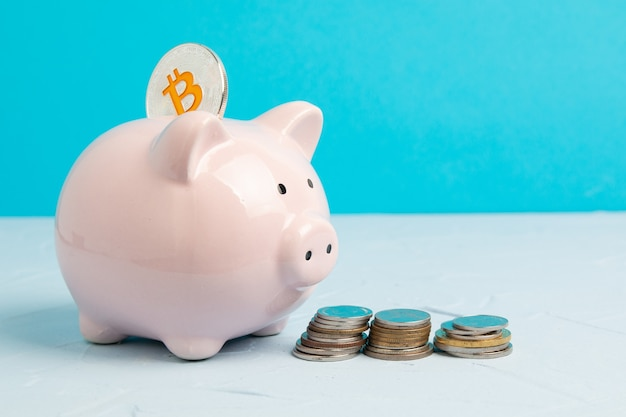 Pink piggy bank on blue space with bitcoin and coin