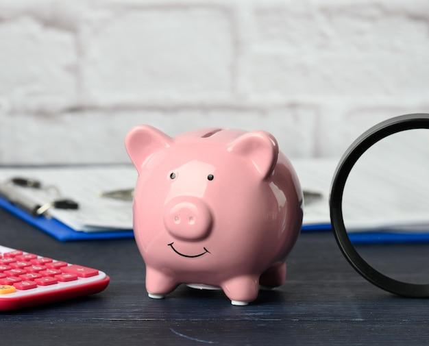 Розовая копилка, калькулятор и лупа на столе