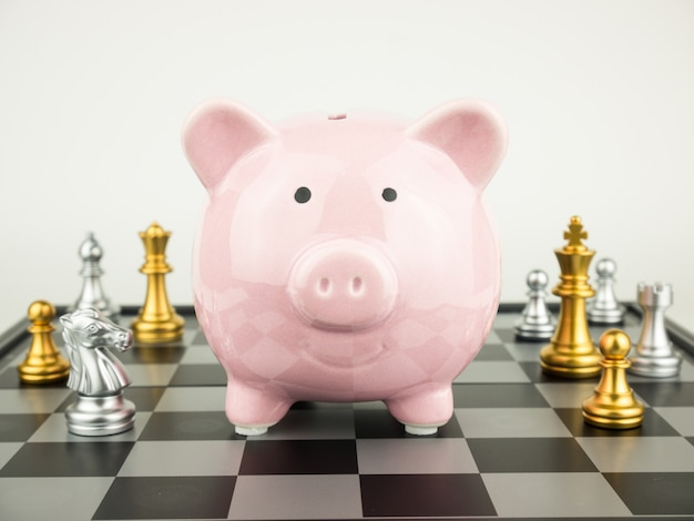 Pink piggy bank and chess pieces on board