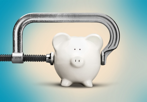 Pink piggy bank and clamp on background