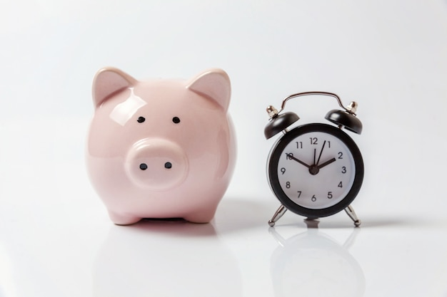 Pink piggy bank and classic alarm clock