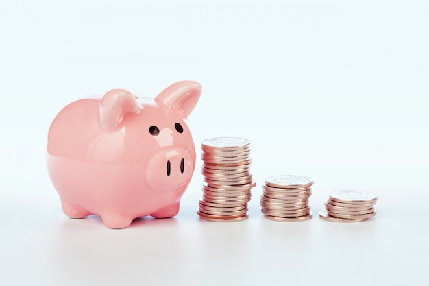 Pink piggy bank and coins isolated on white
