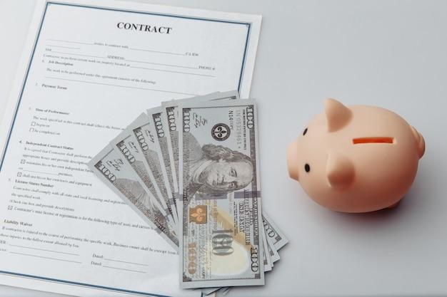 ピンクの貯金箱、白いテーブルの上の契約とお金。経済と経営の財務概念。
