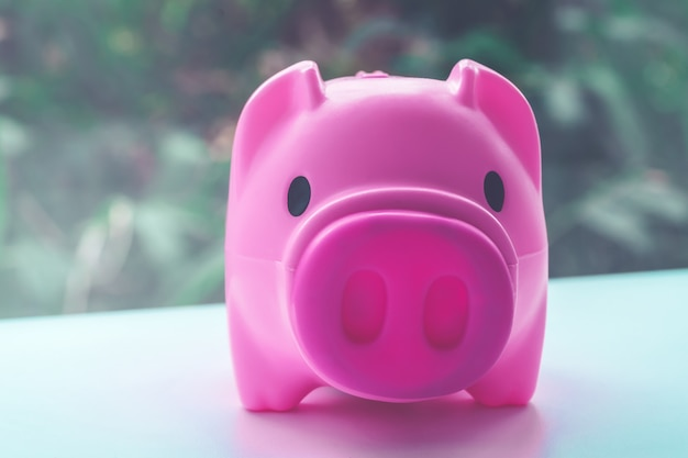 Pink piggy bank in for finance concept in vintage tone