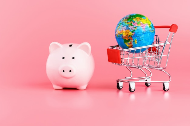 Pink piggy bank and a globe on a shopping cart on a pink background