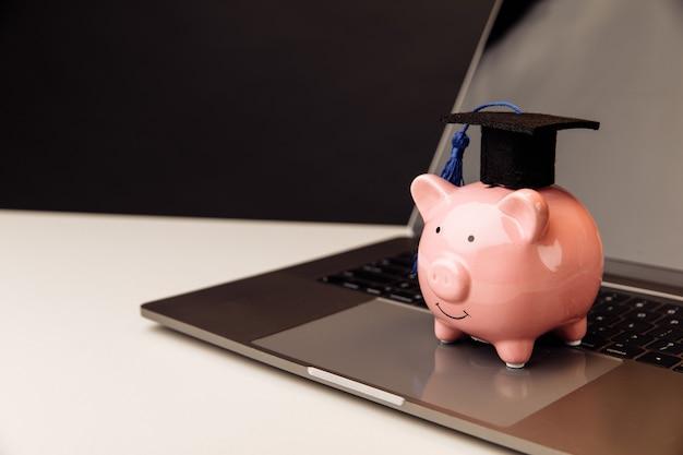 Розовая копилка в кепке на клавиатуре. онлайн-образование.