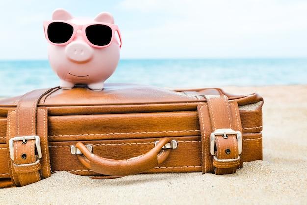 Розовая копилка в солнцезащитных очках на кожаном дорожном футляре на фоне морского пляжа.