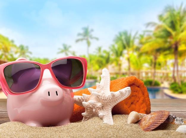 Розовая копилка в солнцезащитных очках на фоне морского бассейна. экономия на концепции отпуска