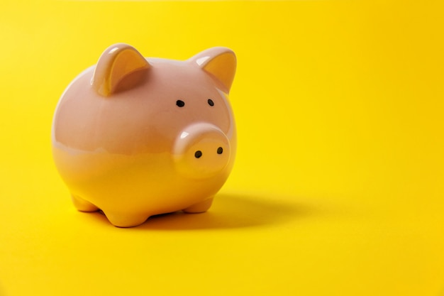 Pink piggy bank isolated on yellow background