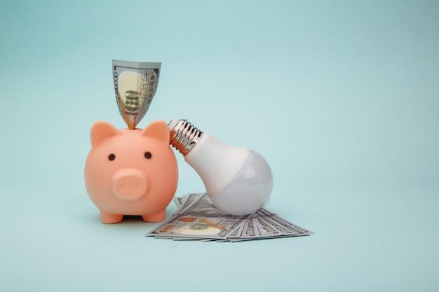 파란색 배경, 절전 개념에 핑크 돼지 저금통, 램프 및 돈 지폐