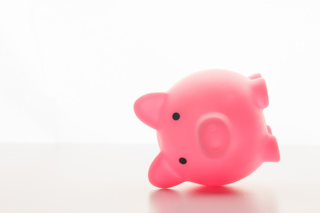 Pink piggy bank lying on its side isolated on white