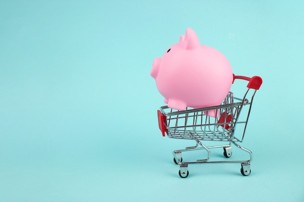 Pink piggy bank in mini shopping cart on blue background. saving money for sales of the year, black friday concept.