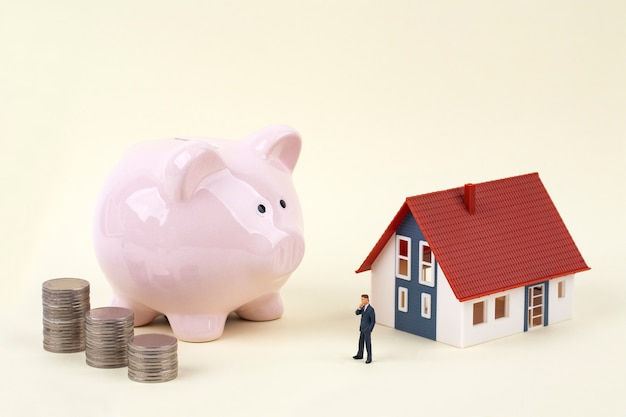 Pink piggy bank and miniature businessman with model house