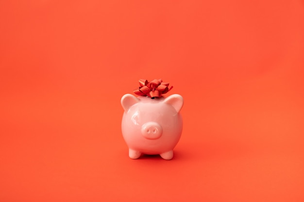 Розовый копилка на красном фоне. рецепт инвестиций и сбережений