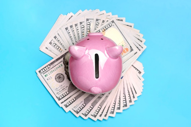 Розовая копилка на фоне банкноты долларов покупка, продажа, инвестиции, банковское дело, кредит, страхование