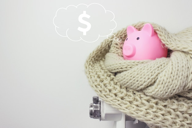Pink piggy bank in the shape of pig with digital hologram dollar in cloud thought above his head on blue background. glowing dollar sign