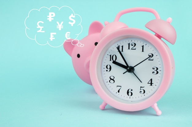 Pink piggy bank in the shape of pig with digital hologram world currencies in cloud thought above his head on blue background. time to saving world currencies.
