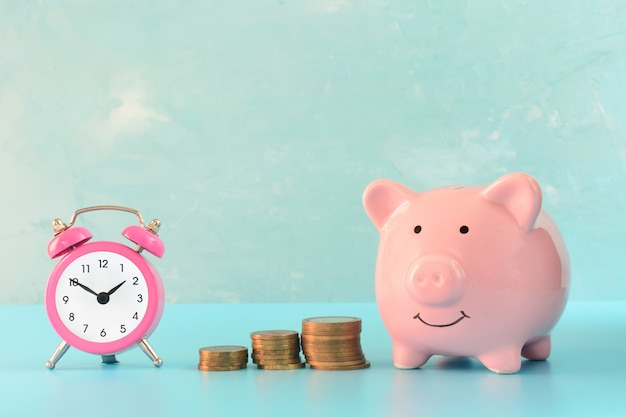 Pink piggy bank next to a small alarm clock and three stacks of coins