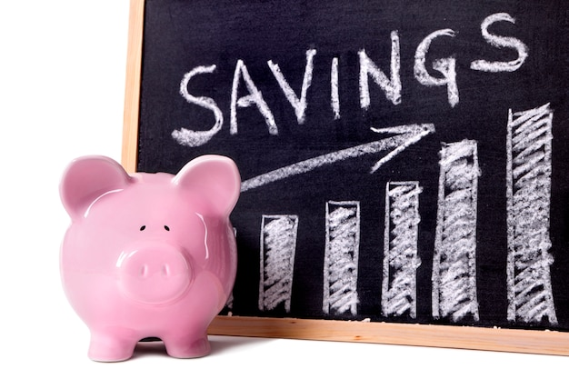 Pink piggy bank standing next to a blackboard with savings growth chart.