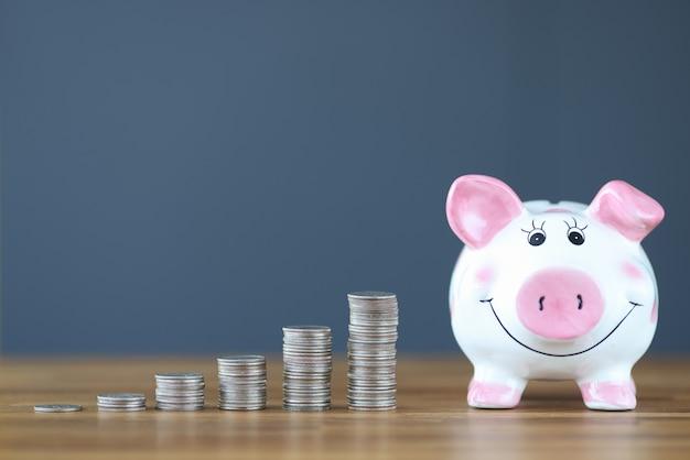 핑크 돼지 저금통 동전 더미 근처 테이블에 서. 사업 투자 개념