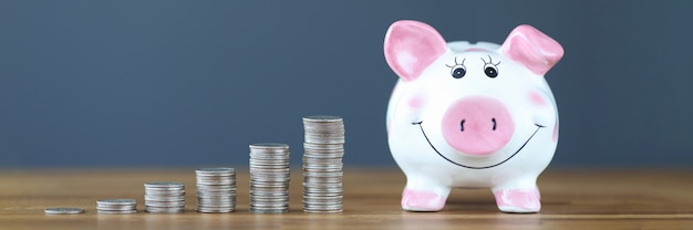 Pink piggy bank standing on table near heaps of coins business investment concept