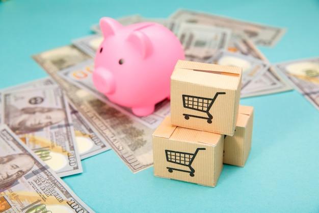 ピンクの貯金箱、3つの配達用ボックス、青のドル紙幣。