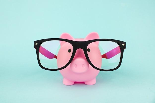안경을 쓴 핑크 돼지 저금통. 절약 경제 개념입니다.