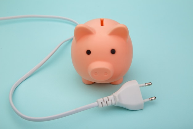 Pink piggy bank and white cord, power savings concept