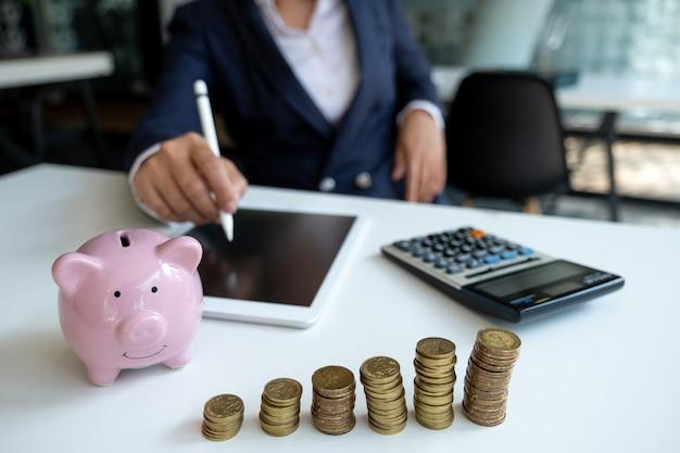 Розовая копилка с деловой женщиной в офисе, экономящая на новой бизнес-цели и концепции выхода на пенсию
