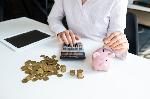 Pink piggy bank with business woman in office saving for new business target and retirement concept