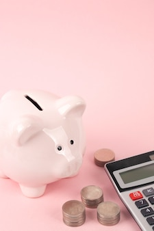 Pink piggy bank with calculator on pink