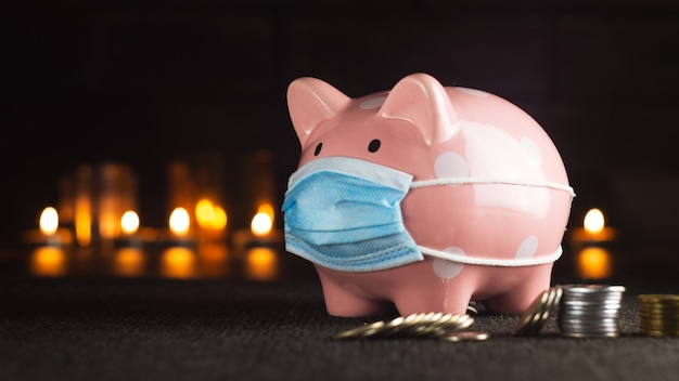 Pink piggy bank with coins on a dark background