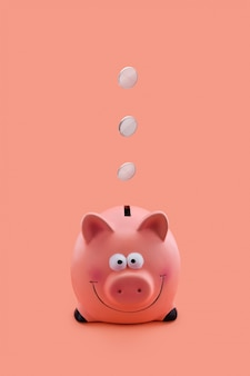 Pink piggy bank with coins falling down