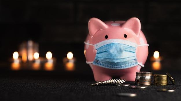 暗い背景にコインとピンクの貯金箱